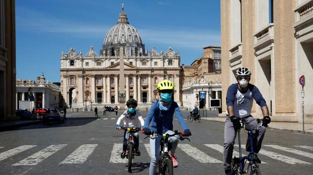 People wearing protective face mask bike in front of St. Peter's Square due to the coronavirus disease (COVID-19) outbreak, at the Vatican May 3, 2020.(REUTERS)