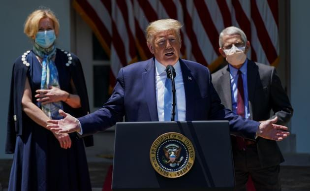 US President Donald Trump speaks about administration efforts to develop a novel coronavirus vaccine as Dr. D Birx, White House Covid-19 response coordinator, and NIAID Director Dr. A Fauci listen during a Covid-19 pandemic response event in the Rose Garden at the White House in Washington, US.(REUTERS)