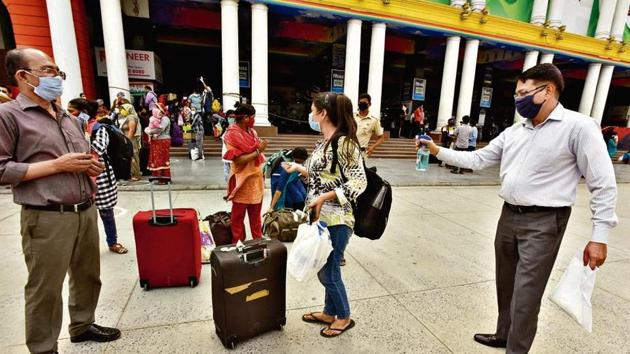 A passenger, upon arriving at the New Delhi railway station, sprays disinfectant over the luggage of his family members.(Sonu Mehta/HT PHOTO)