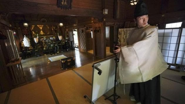 A priest prepares a livestream prayer at Onoterusaki Shrine.The shrine also accepted worshippers' messages, which were printed on a virtual wooden tablet and offered to Shinto gods to keep away evil spirits and the epidemic.(AP)