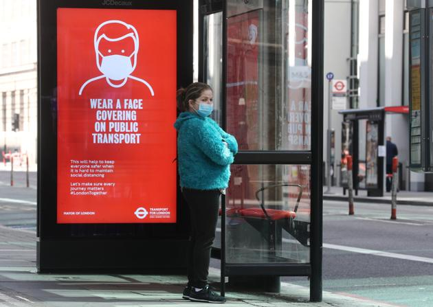 A woman wearing a face mask waits at a bus stop in London, following the outbreak of the coronavirus disease (COVID-19), London, Britain, May 18, 2020.(REUTERS)