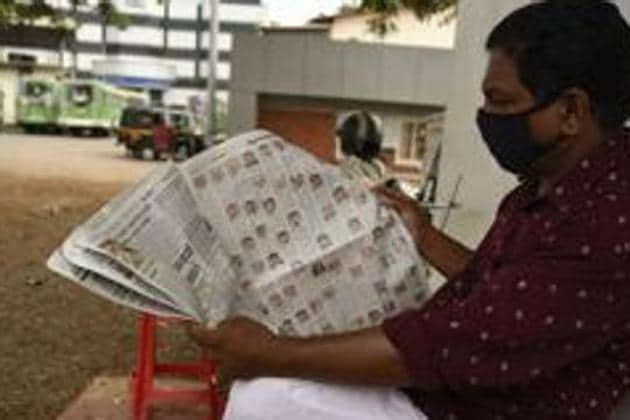 A man reads a newspaper at a bus terminus in Kochi, Kerala. Newspapers readers are highly likely to jump to a page or section of their preference. This guarantees a significant number of eyeballs in direct correlation to the popularity of a certain section or page.(AP Photo)