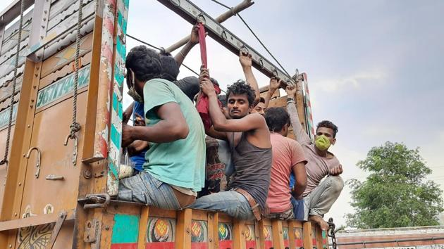 Despite the government's efforts to arrange vehicles to transport them, the labourers can be seen moving on the road.(HT Photo)