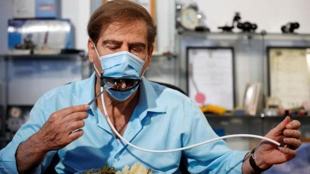 Meir Gitelis, co-developer of an Israeli company, eats while wearing a mask fitted with a mechanical mouth that opens to enable diners to eat without taking it off.(REUTERS)