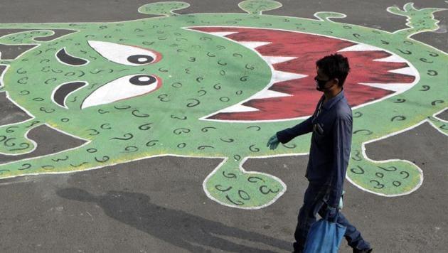 A man walks past a grafitti depicting the coronavirus, during a lockdown to control its spread in Mumbai, India, Saturday, May 16, 2020.(AP photo)