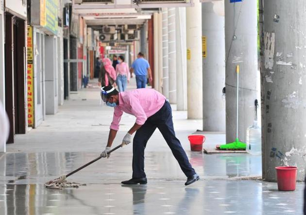 A man cleaning the corridor before opening a shop at the Plaza in Sector 17 in Chandigarh on Tuesday.(Ravi Kumar/HT)