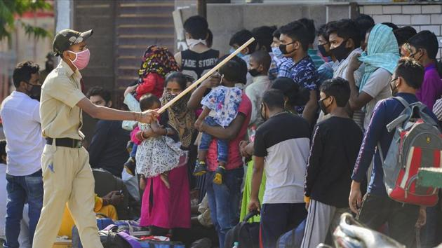 A policeman controls migrants who were waiting along with their families at a government school to get screened before boarding buses for their native places, during ongoing Covid-19 lockdown, in New Delhi on Wednesday.(PTI Photo)