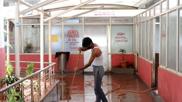 A worker cleans toilets at a bus station in Telangana, on Tuesday.(AFP Photo)