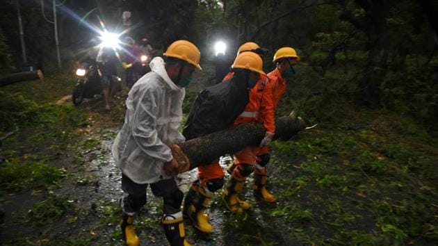 Members of National Disaster Response Force (NDRF) remove a branch of an uprooted tree after Cyclone Amphan made its landfall, in West Bengal's Digha, on Wednesday.(Reuters Photo)