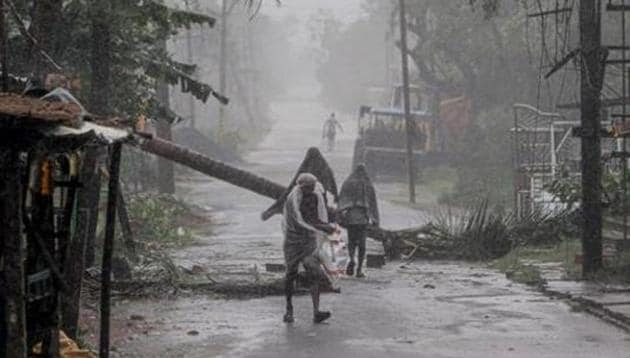 People make way through gusty winds as super cyclone Amphan makes landfall, near Dhamara Port in Bhadrak district, Wednesday, May 20, 2020.(PTI)