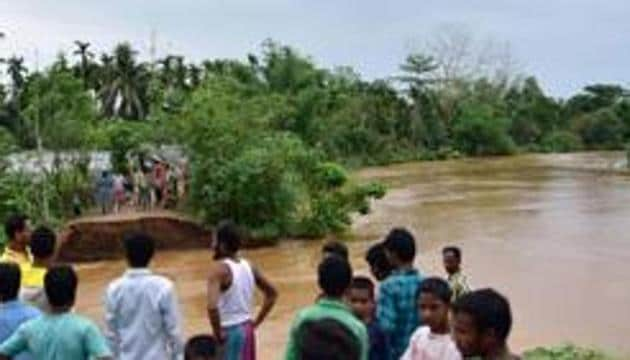 Nagaon: Villagers watch a washed away road after flooding by Borpani River due to incessant rainfall for the past two days, at Madhab Para near Kampur in Nagaon district of Assam(PTI)