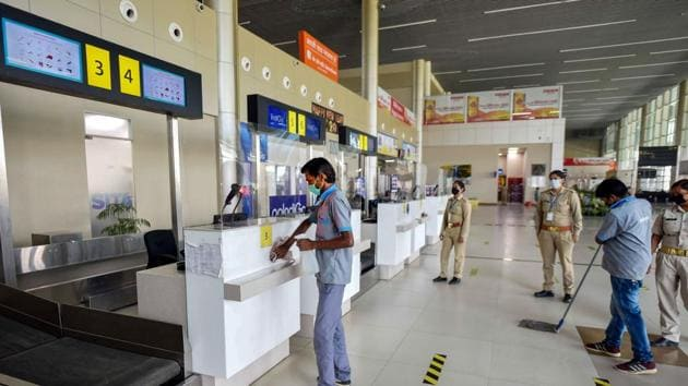 Security personnel stand guard as airport staff sanitse Prayagraj airport during the fourth phase of Covid-19 nationwide lockdown, in Prayagraj on Sunday.(PTI Photo)