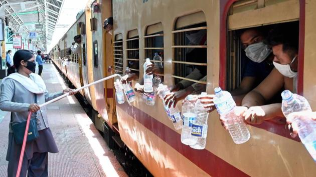 A railway employee refills water bottles of migrant workers sitting inside a special train bound to their home state amid the lockdown in Jabalpur, on May 23. IMD's bulletin added that heatwave conditions were likely over Punjab, Haryana, Chandigarh, Delhi, Rajasthan, Uttar Pradesh, Madhya Pradesh, Vidarbha (Maharashtra) and Telangana over the next 4-5 days. (PTI)