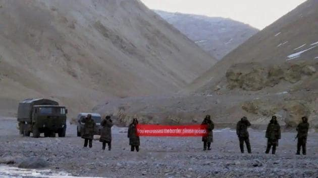 In this May 5, 2013 photo, Chinese troops in Ladakh hold a banner that asked Indian troops to move back.(AP Photo)