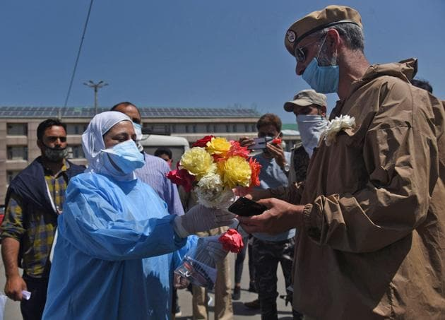 A cop offering flowers to a doctor outside LD Hospital in Srinagar following outrage over reports of harassment of doctors by policemen amid Covid-19 lockdown.(Waseem Andrabi/HT)