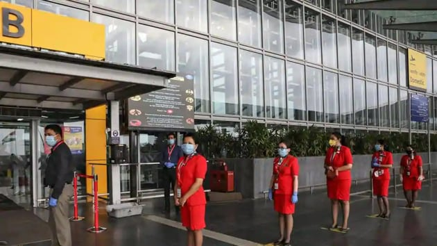 AirAsia staff members stand on social distancing markings, as they wait to enter Netaji Subhas Chandra Bose International Airport in Kolkata, on Wednesday.(Reuters Photo)