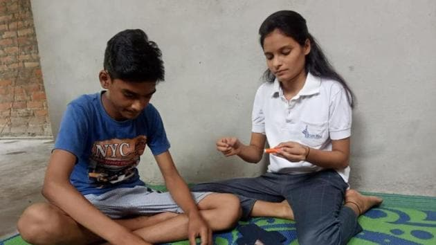 Deeksha and her brother Himanshu (above) and Aneesha and her brother Anmol (left) busy making sanitary pads.(HT Photo)