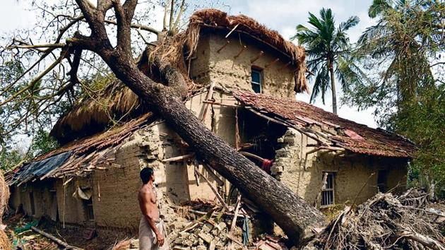 A man stands next to a house damaged in Cyclone Amphan in Sunderbans region's Sagar island.(by special arrangement)