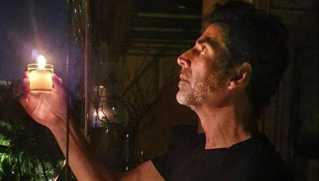 Bollywood actor Akshay Kumar holds a candle in response to Prime Minister Narendra Modi's call to light lamps to express solidarity with the country's fight against the novel coronavirus.(PTI)