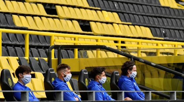 Schalke substitutes wearing protective face masks maintain social distance, as play resumes behind closed doors following the outbreak of the coronavirus disease (COVID-19).(REUTERS)