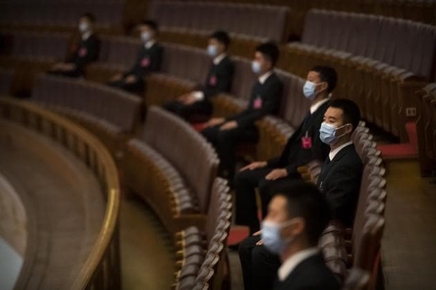 Security personnel wearing face masks to protect against the new coronavirus sit before the closing session of China's National People's Congress (NPC) at the Great Hall of the People in Beijing.(AP)