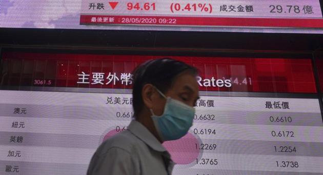 A man wearing a face mask walks past a bank electronic board showing the Hong Kong share index at Hong Kong Stock Exchange, Thursday, May 28, 2020.(AP photo)