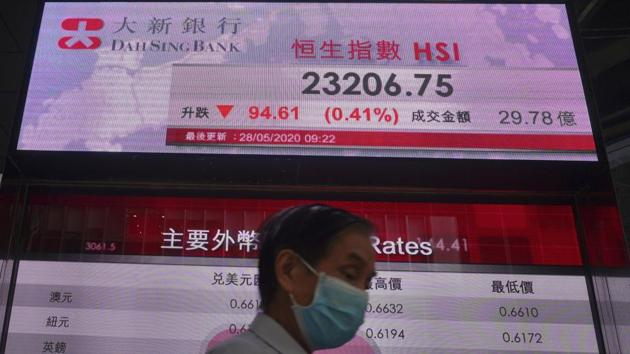 A man wearing a face mask walks past a bank electronic board showing the Hong Kong share index at Hong Kong Stock Exchange on Thursday.(AP File Photo)