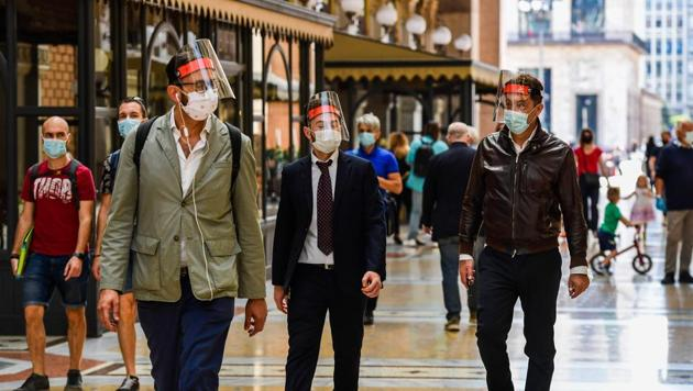 People wearing a face mask and shield walk across the Vittorio Emanuele II shopping mall in Milan on May 18, 2020 during the country's lockdown aimed at curbing the spread of the COVID-19 infection, caused by the novel coronavirus.(AFP)