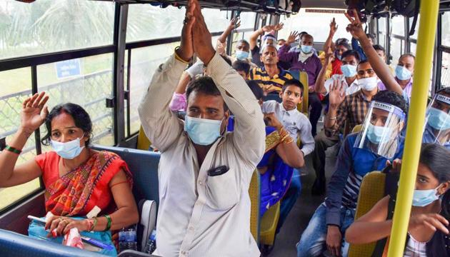 Stranded migrants arriving at the Birsa Munda International Airport by a special flight from Mumbai react while being carried in a bus for check-out, during ongoing Covid-19 lockdown, in Ranchi, Thursday, May 28, 2020.(PTI photo)