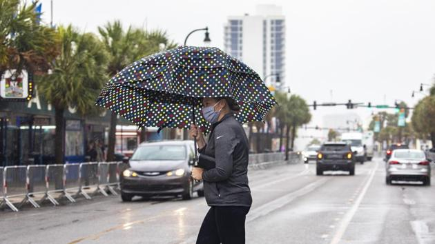 A pedestrian, carrying an umbrella and wearing a mask, crosses Ocean Boulevard in Myrtle Beach, as Tropical Storm Bertha lashes the South Carolina coast on Wednesday.(AP Photo)