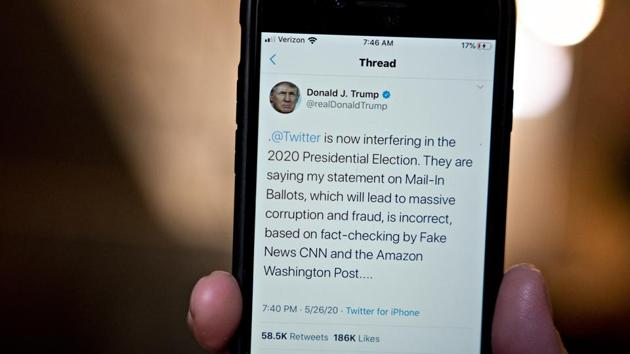 A Twitter election interference tweet by U.S. President Donald Trump is displayed on a smartphone in an arranged photograph taken in Arlington, Virginia, U.S., on Wednesday, May 26, 2020. President Donald Trump threatened to regulate or shutter social media companies -- a warning apparently aimed at Twitter Inc. after it began fact-checking his tweets. Photographer: Andrew Harrer/Bloomberg(Bloomberg)