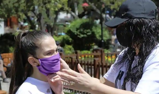 A mother wearing a face mask for protection against the coronavirus, adjusts her daughter's mask in Kugulu public garden, in Ankara, Turkey, Wednesday, May 13, 2020.(AP)
