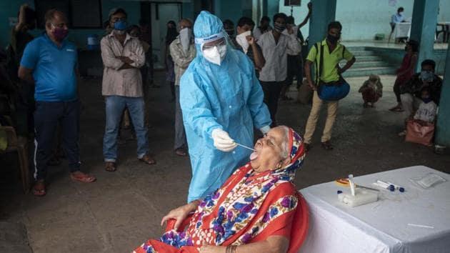 A healthcare worker collects an oral swab sample of a senior citizen woman at Sane Guruji Smarak, Sinhagad road.(Pratham Gokhale/HT Photo)