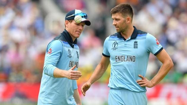 England's captain Eoin Morgan (L) speaks with teammate England's Mark Wood during the 2019 Cricket World Cup group stage match between England and Australia at Lord's Cricket Ground in London on June 25, 2019.(AFP)