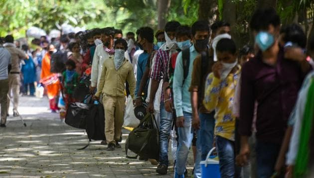 Migrants wait to get screened and register for transit buses that will ferry them to railway stations for Shramik Special trains, at Vasant Kunj in New Delhi on Thursday.(Amal KS/HT PHOTO)