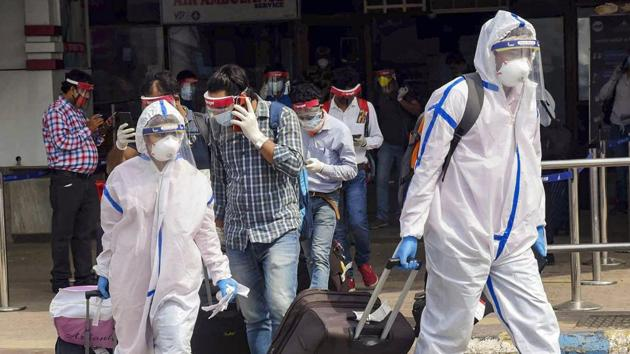 Passengers wearing PPE kits check-out from the Jai Prakash Narayan International Airport upon their arrival from Bengaluru in Patna.(PTI)
