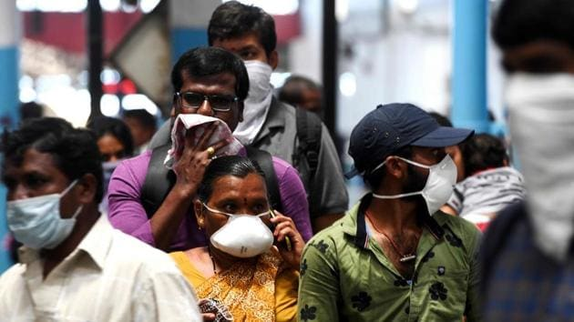 Passengers wear facemasks amid concerns over the spread of the COVID-19 novel coronavirus at M.G.R.Central railway station in Chennai on March 16, 2020.(AFP)