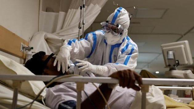 A medical worker wearing personal protective equipment takes care of a patient suffering from the coronavirus disease, at a hospital in Delhi on Thursday.(Reuters Photo)