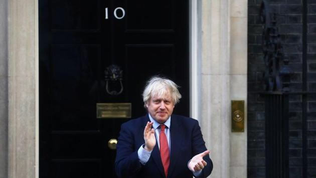 Britain's Prime Minister Boris Johnson applauds outside 10 Downing Street during the Clap for our Carers campaign in support of the NHS.(REUTERS)
