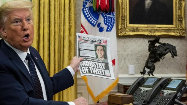 """US President Donald Trump speaks while holding up a copy of the New York Post newspaper before signing an executive order in Washington, SC, US. Trumpcalled out a single Twitter employee Thursday in a tweet complaining that the platform's decision tofact checkhis tweets on mail balloting could """"taint"""" the election.(Bloomberg)"""