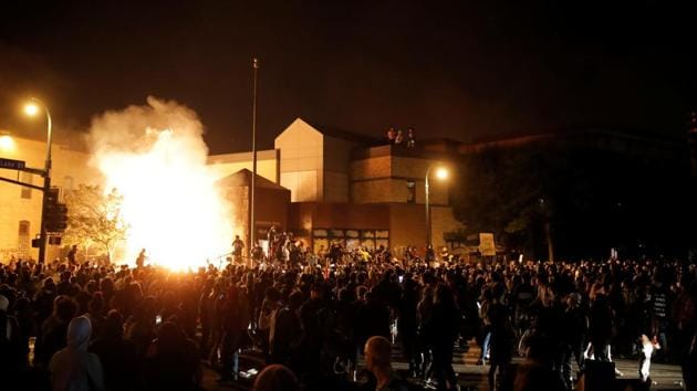 Protesters gather around after setting fire to the entrance of a police station as demonstrations continue after a white police officer was caught on a bystander's video pressing his knee into the neck of African-American man George Floyd, who later died at a hospital, in Minneapolis, Minnesota, US.(REUTERS)