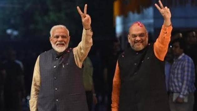 Prime Minister Narendra Modi (L) and president of the ruling Bharatiya Janata Party (BJP) Amit Shah gesture as they celebrate the victory in India's general elections, in New Delhi on May 23, 2019.(AFP)