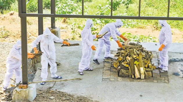 Municipal workers wearing protective suits cremate the body of Covid-19 victim in Karad, Maharashtra.(PTI)