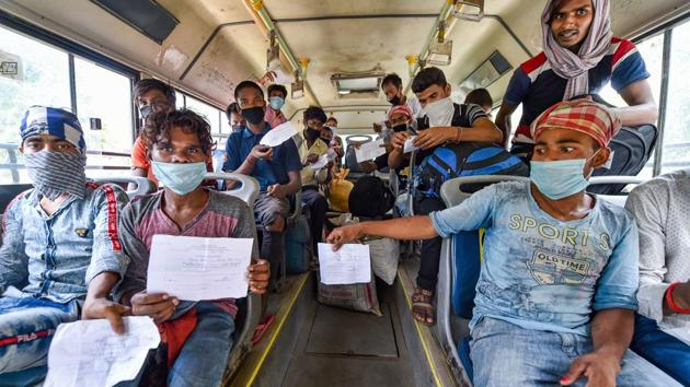 Migrants travelling to West Bengal show their medical certificates before boarding a bus to the railway station, during the ongoing nationwide lockdown, at Yamuna Sports Complex in New Delhi.(PTI)