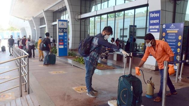 Passengers get their luggage sanitized and get thermal check up at Pune airport.(Shankar Narayan/HT PHOTO)