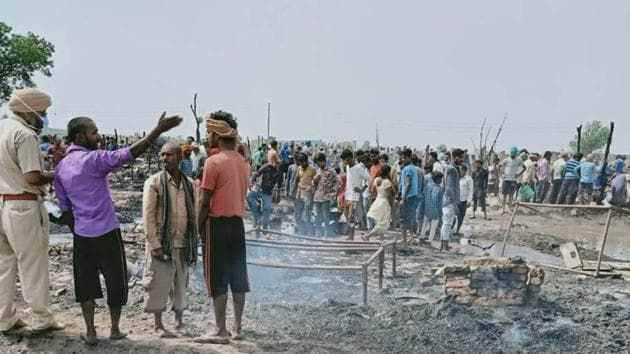 Cops inspecting the site where a fire broke out, destroying several shanties in Ludhiana on Friday.(HT PHOTO)
