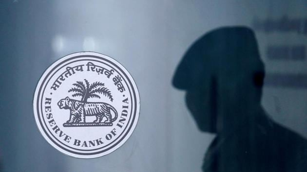 A security guard's reflection is seen next to the logo of the Reserve Bank Of India at the RBI headquarters in Mumbai.(REUTERS)