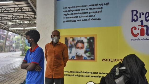 Indians wearing masks stand next to a signage that urges people to wash their hands and wear masks to protect against the COVID-19 pandemic in Kerala.(AP)