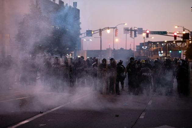 A cloud of tear gas thrown by police hangs in the air near police in riot gear near in Downtown Atlanta, during a protest against the death in Minneapolis police custody of African-American man George Floyd, in Atlanta, Georgia.(REUTERS)