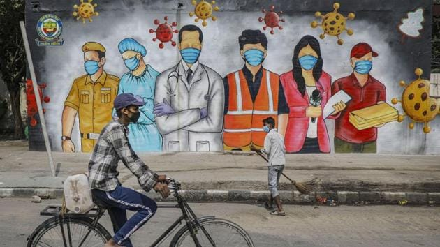 A cyclist rides past a mural that reads 'A Big Salute To Corona Warriors', during ongoing COVID-19 lockdown, in New Delhi, Sunday, May 31, 2020.(PTI)